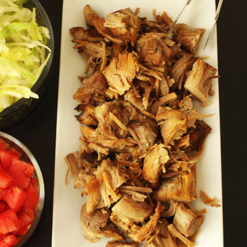 carnitas on platter next to bowls of tomatoes and lettuce