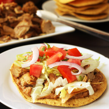 carnitas tostada on plate with other ingredients on table