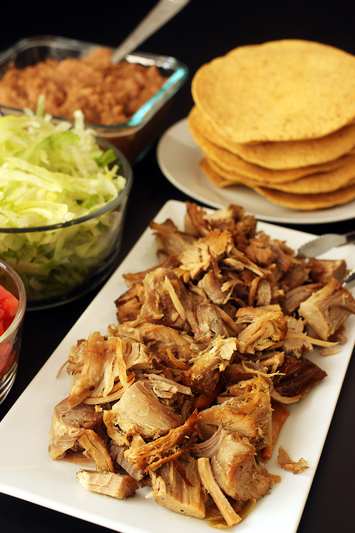 platter of carnitas next to tostada shells and toppings