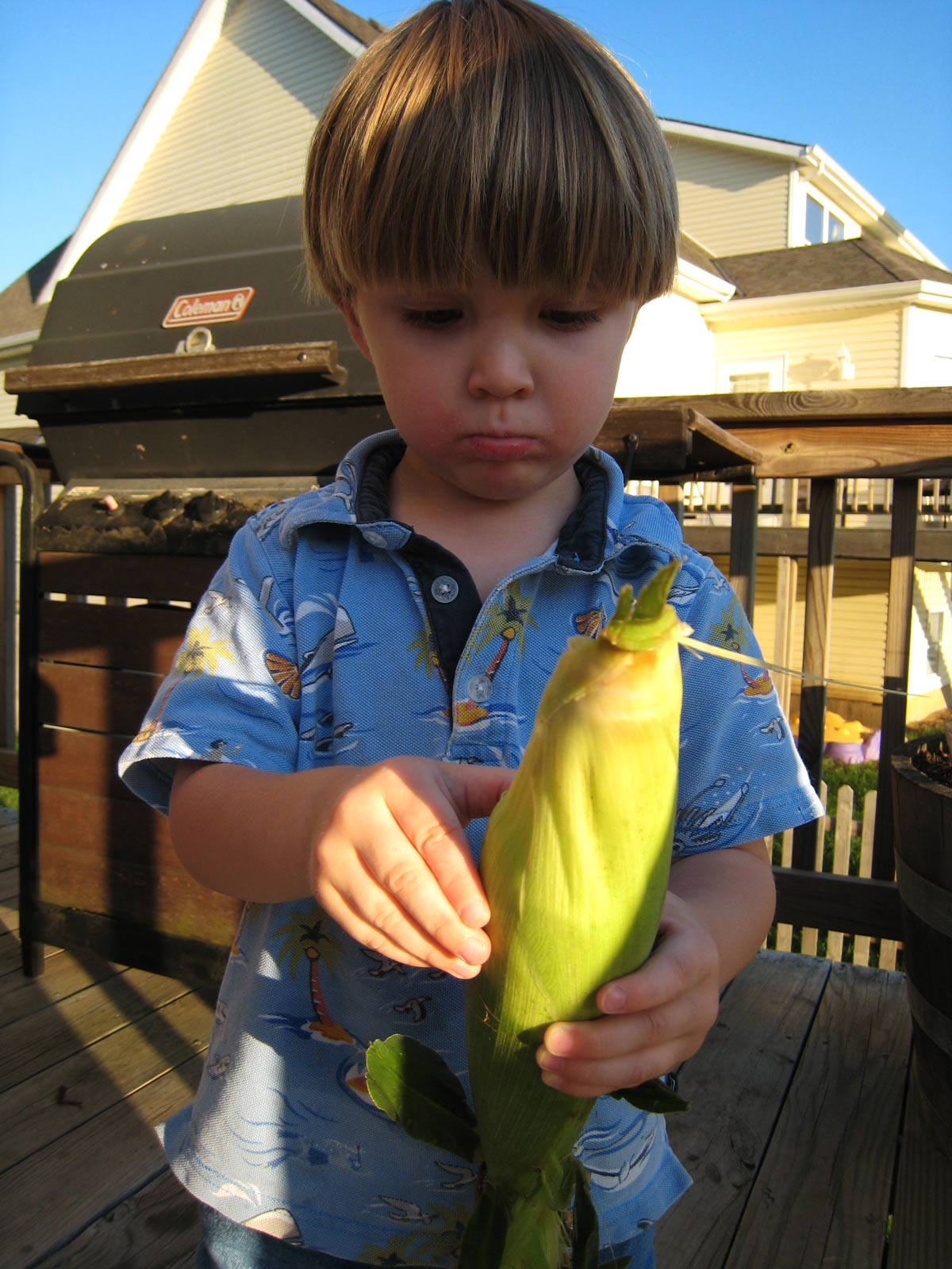 toddler boy on deck holding ear of corn to shuck.