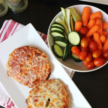 Pizza bagels on plate with bowl of veggies