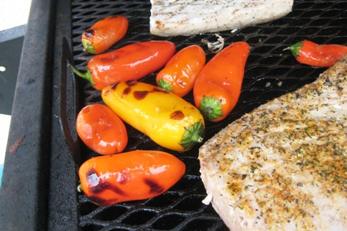 A close up of peppers on a grill