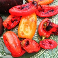 A close up of mini grilled peppers on a plate