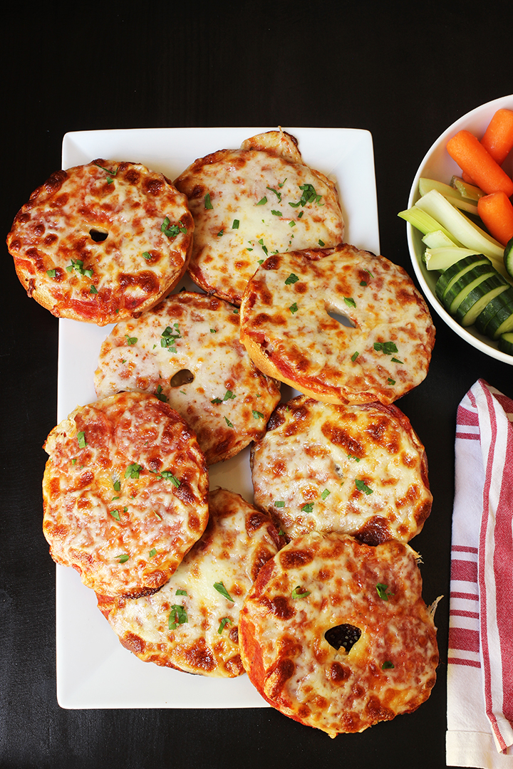 white tray of pizza bagels with red striped cloth and veggie tray