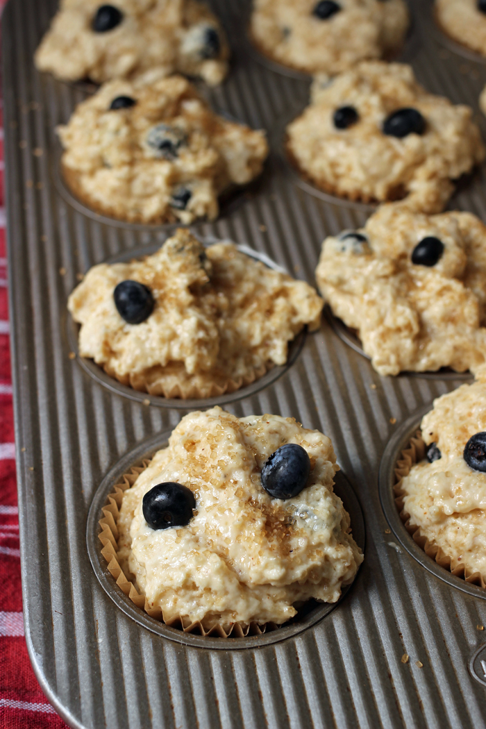 uncooked muffins in pan sprinkled with sugar and blueberries
