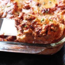 A close up of a slice of lasagna