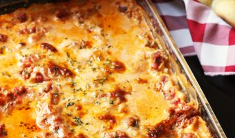 pan of lasagna with salad and rolls