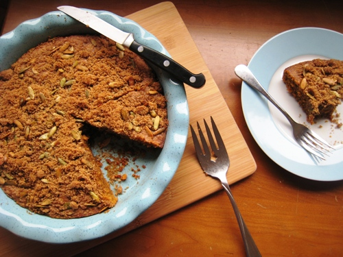 A piece of pumpkin coffee cake on a plate, with full cake