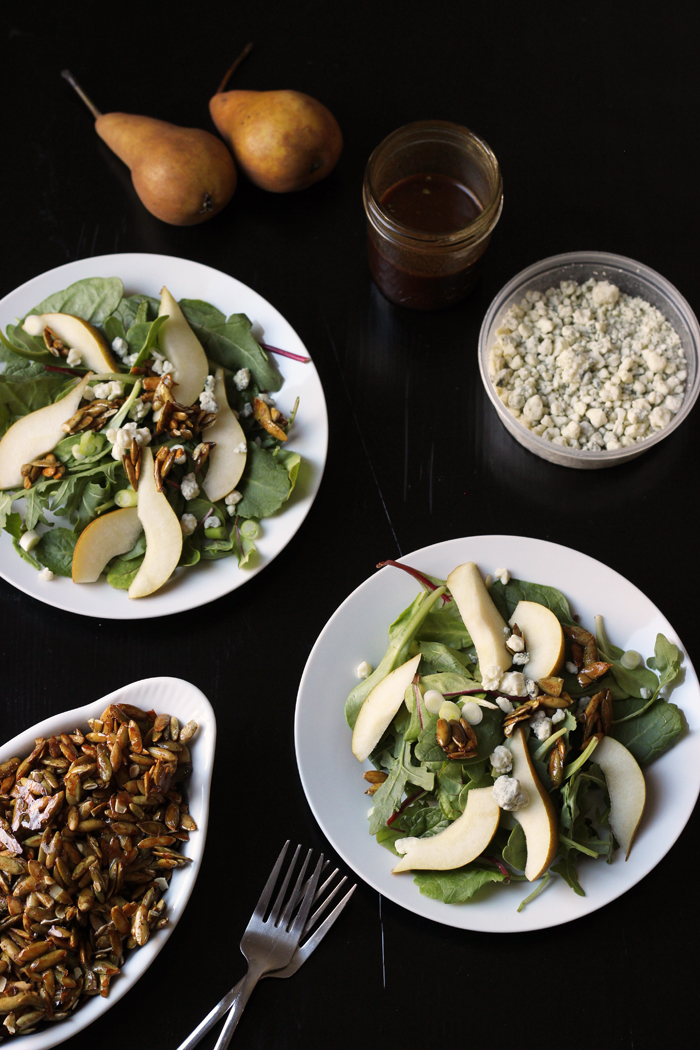 pear salads with bowl of blue cheese and dish of pepitas