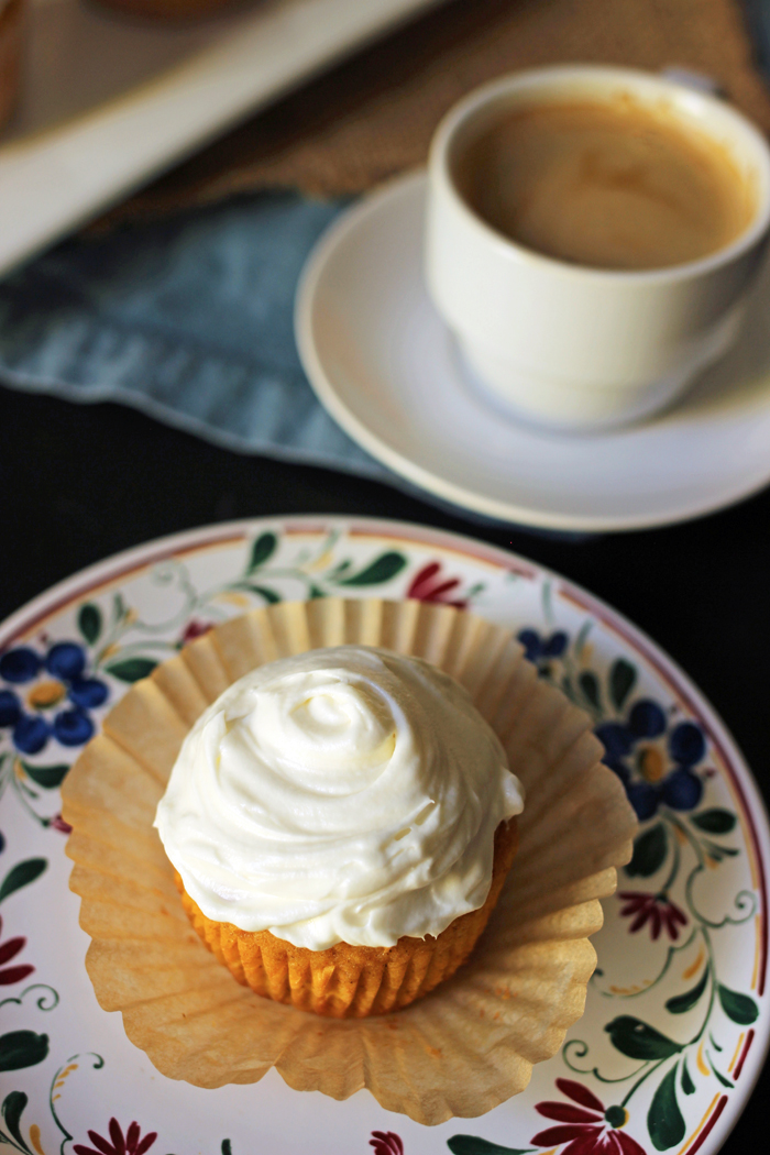 cupcake on flowered plate with paper loosened and coffee cup