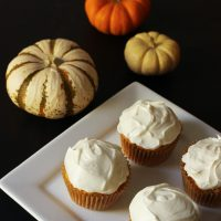 four cupcakes on plate on black table with pumpkins