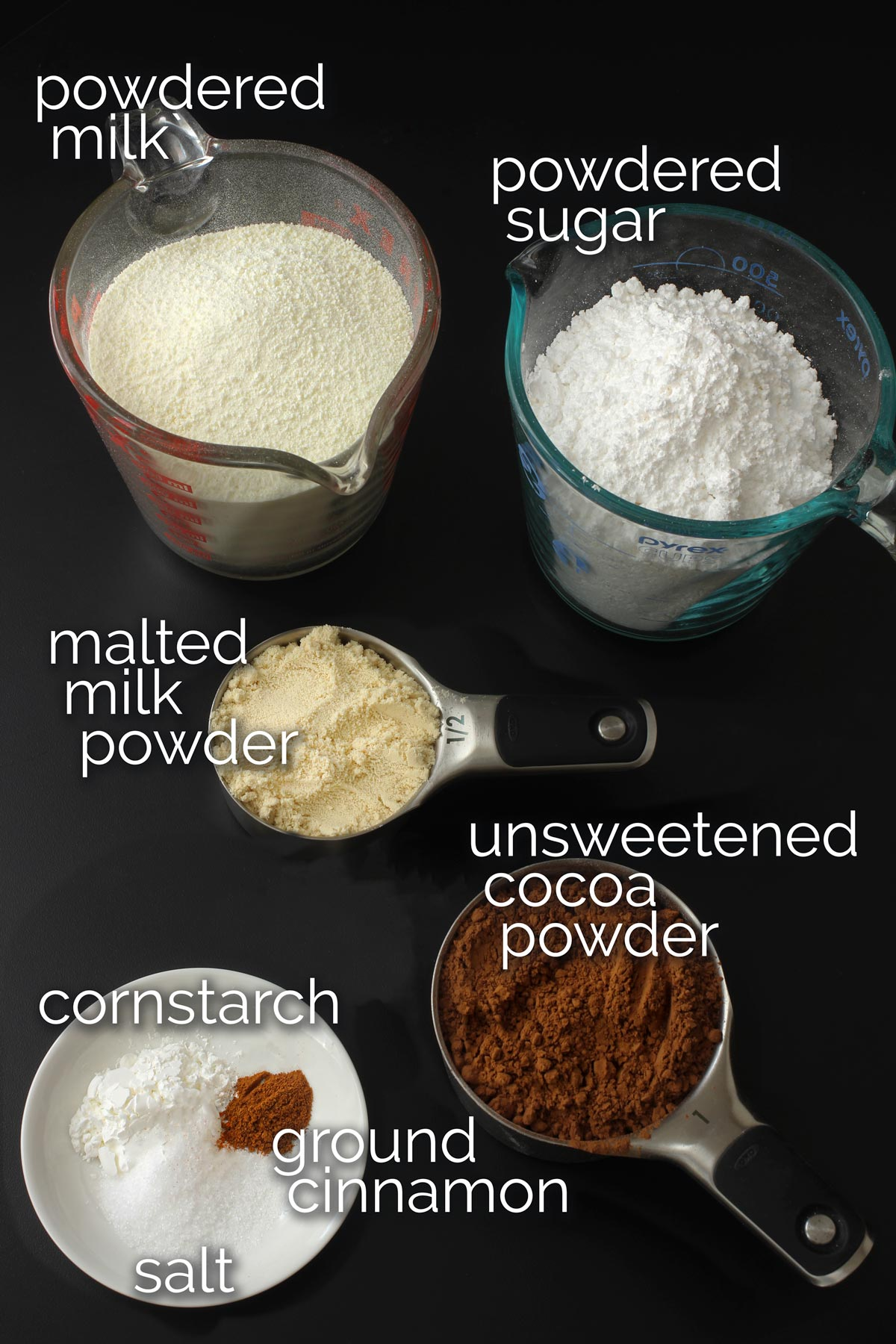 ingredients for malted cocoa mix in measuring cups on black table