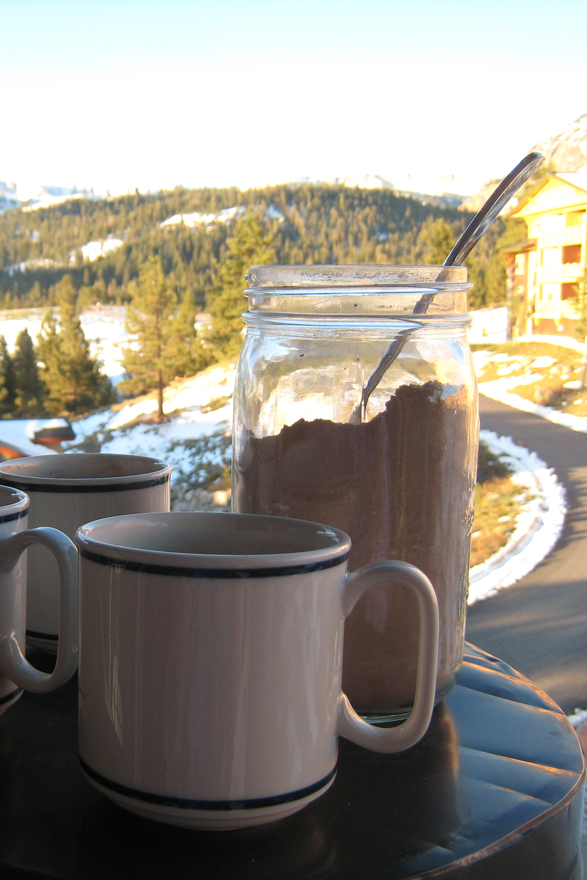 mugs and jar of cocoa mix on balcony pillar with snowy mountains in background