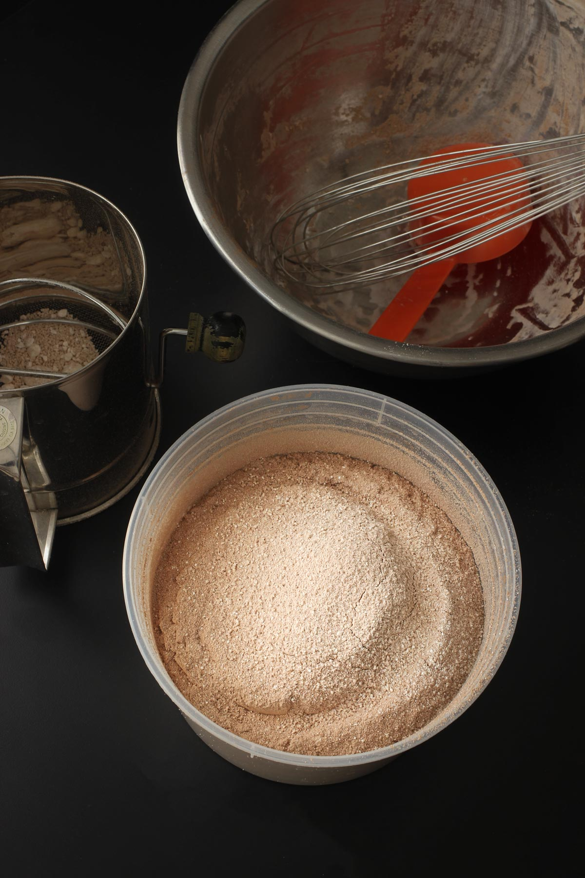 partially empty sifter, empty bowl, whisk, and tub of cocoa mix on black table