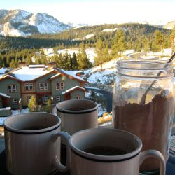 three mugs with a jar of cocoa mix in front of snow covered chalet