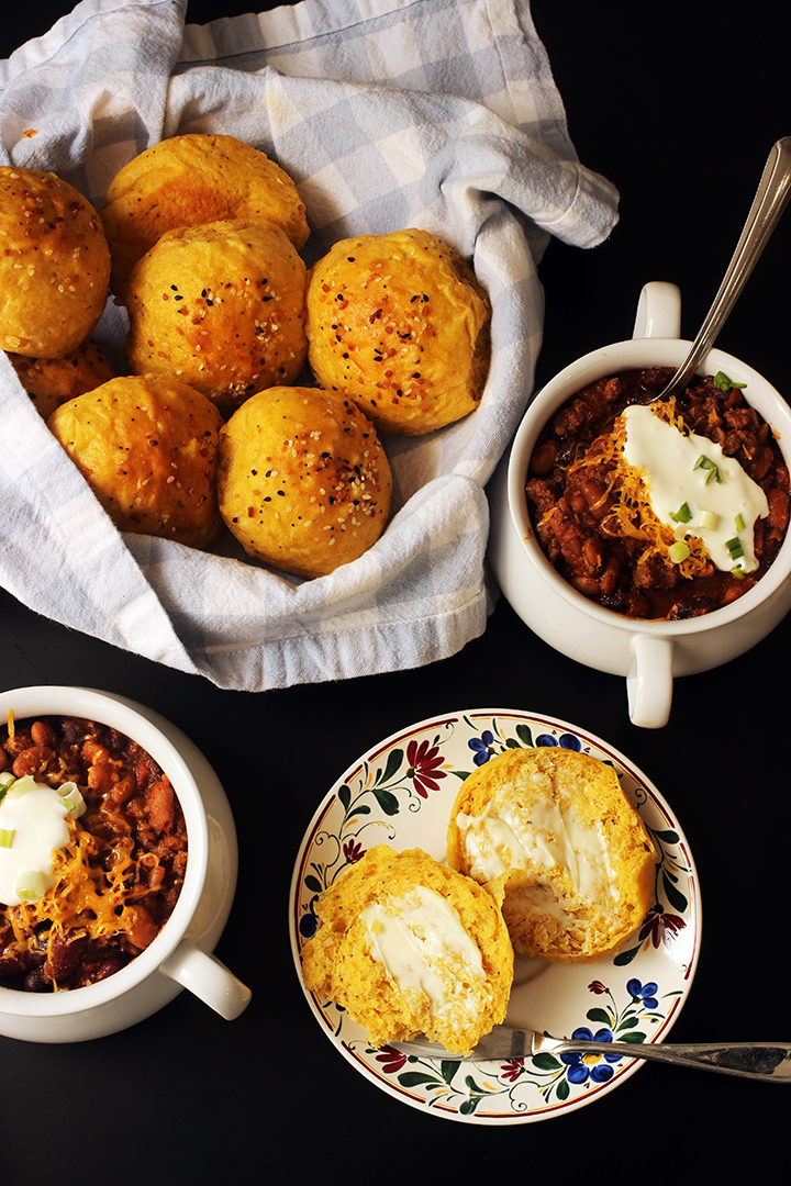 bread basket, bowls of chili, and bread plate with buttered roll