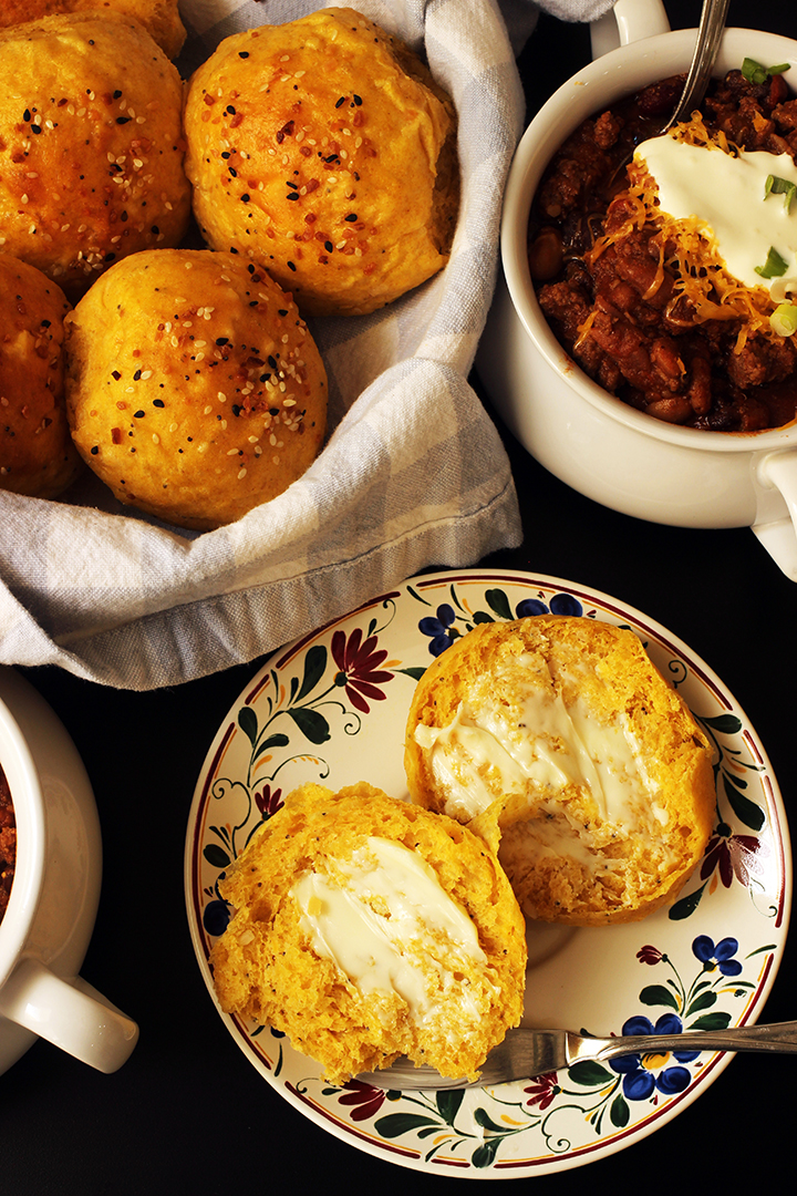 roll on bread plate next to bread basket and bowl of chili