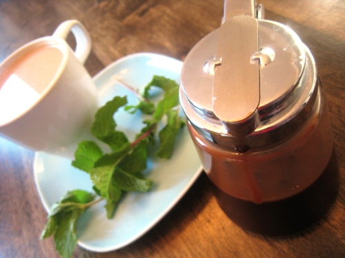 A cup of coffee on a table, with Mint and Syrup