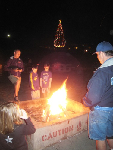 A group of people standing around a bonfire