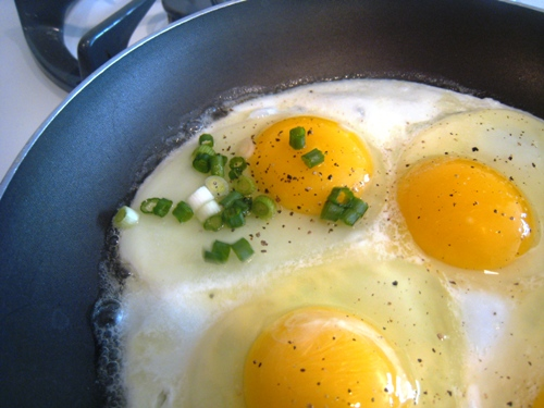 A skillet of fried eggs with scallions