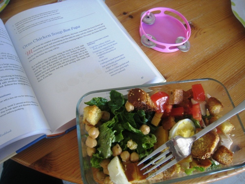 A plate of salad on a table, with cookbook