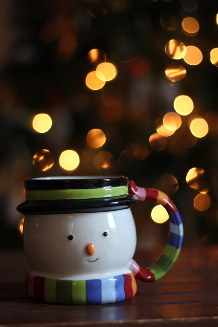snow man mug with twinkle lights in background