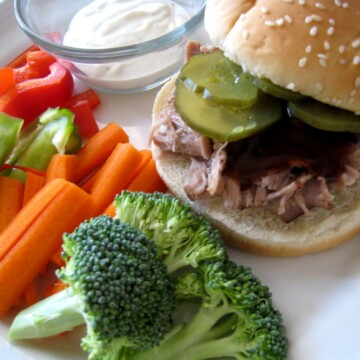 A plate of food with broccoli and pulled pork sandwich