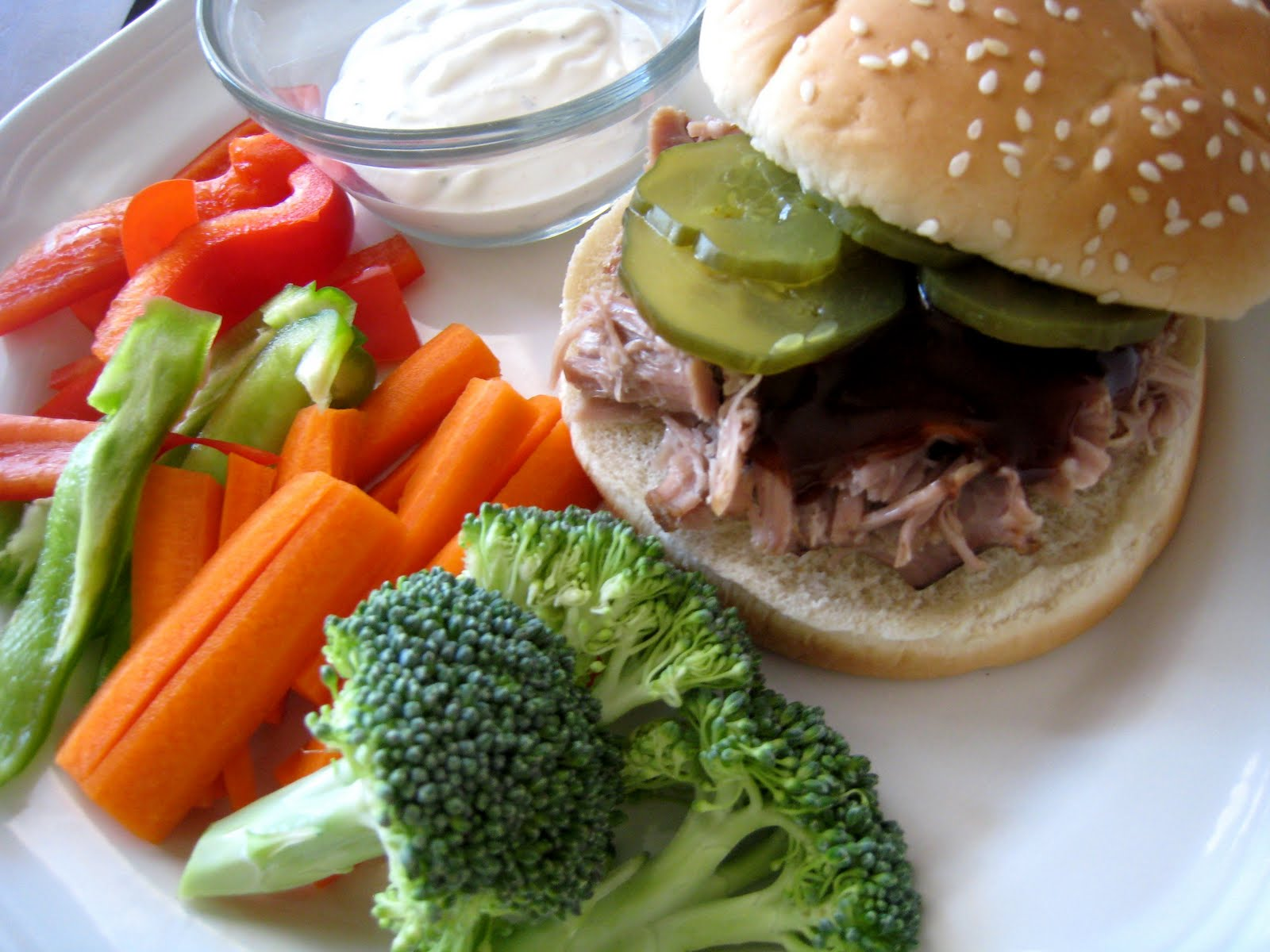A plate of veggies and BBQ Pork sandwich