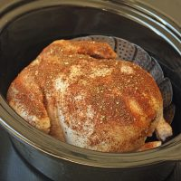 a slow cooker with uncooked seasoned chicken