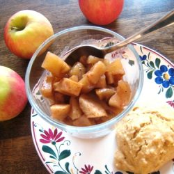 A bowl of compote and apples on table