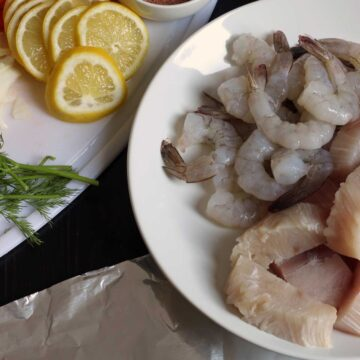 fish and shrimp on plate with lemon