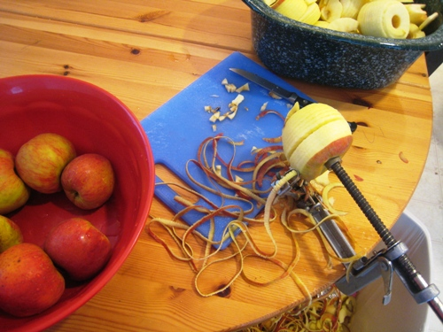 an apple on an apple peeler with bowls of apples
