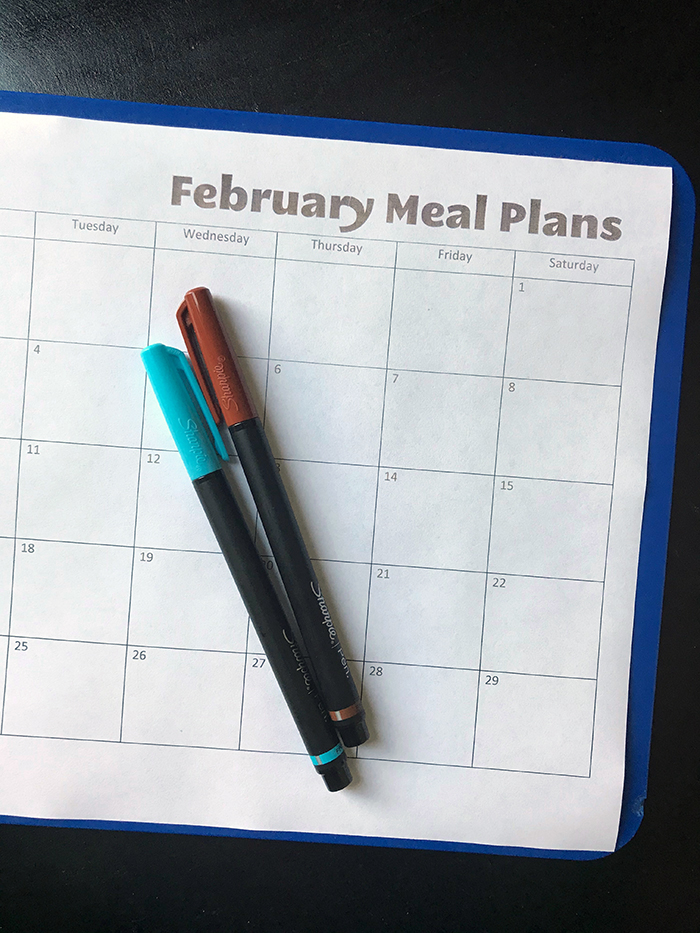 blank meal plan calendar for February on clipboard with pens
