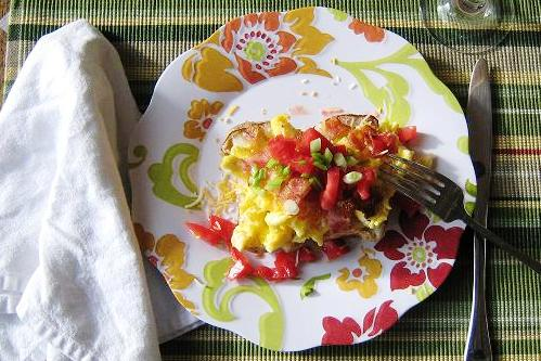 loaded breakfast potato with toppings on a plate