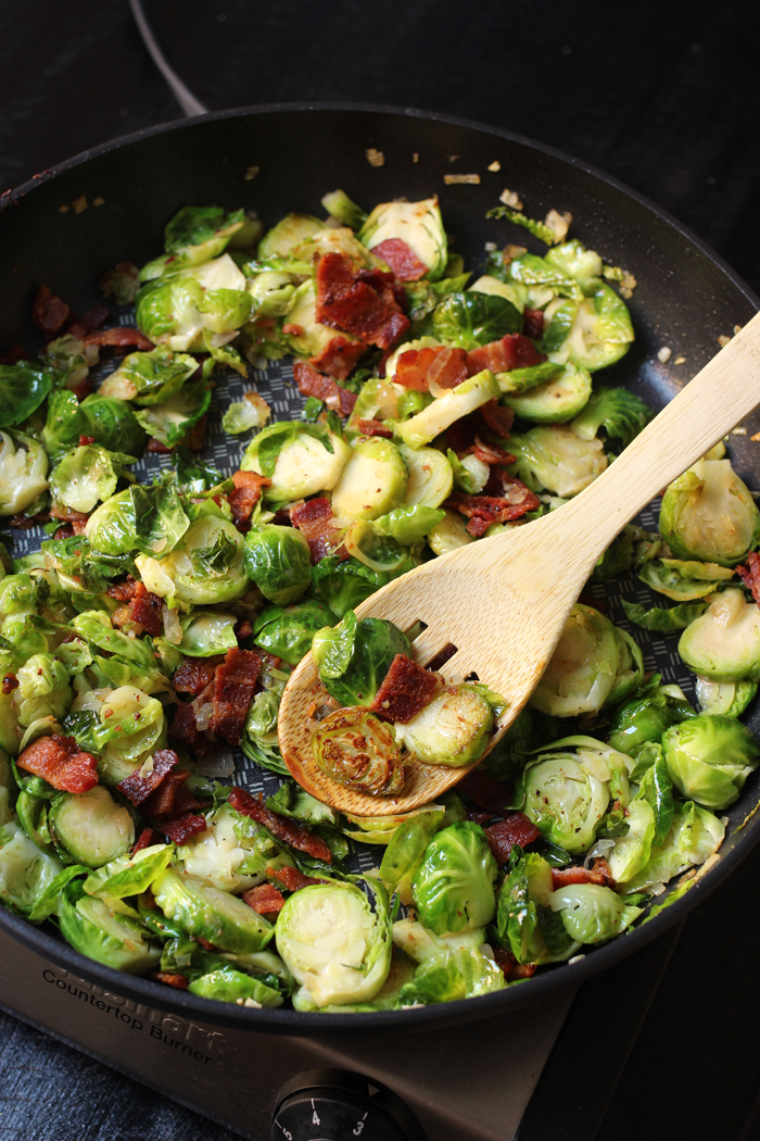 sprouts and bacon in pan stirred with wooden spoon