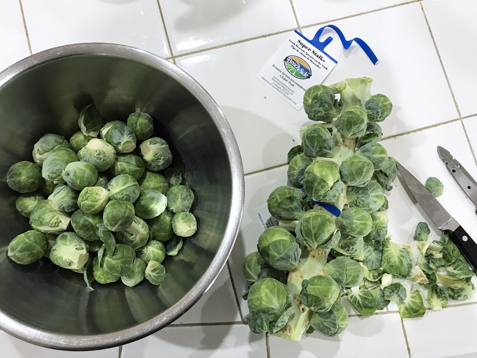 cutting brussels sprouts off stalks on kitchen counter