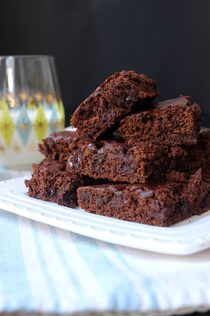 platter of brownies on striped cloth next to glass of milk