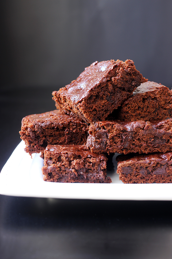 stack of brownies on square white plate