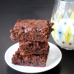 stack of brownies on white plate next to glass of milk