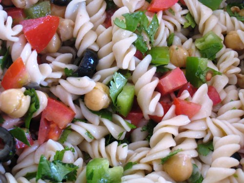 A bowl of pasta salad, with vegetables