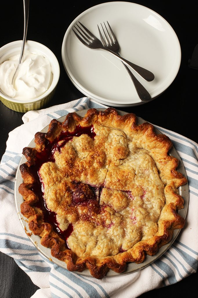 mixed berry pie on table with bowl of cream and pie server