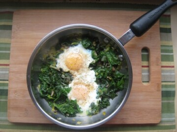 Eggs and Spinach in a skillet on a board