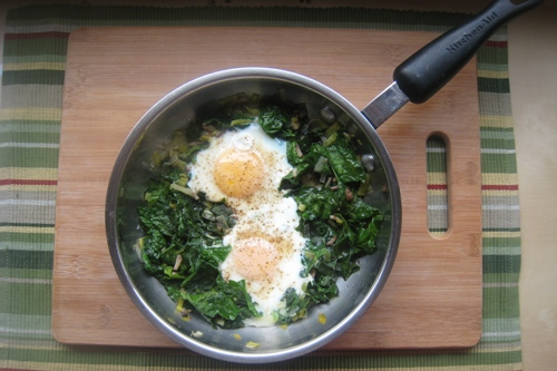 A skillet of poached eggs with spinach