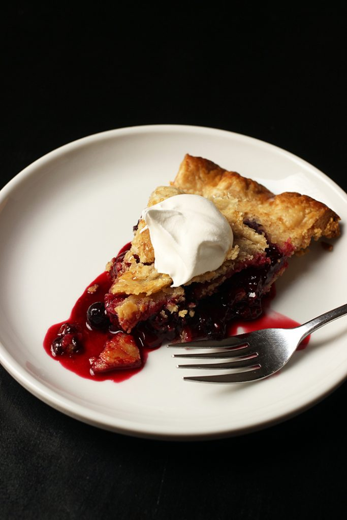 slice of berry pie on plate with whipped topping
