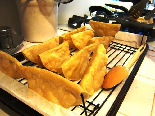 fried taco shells draining on rack