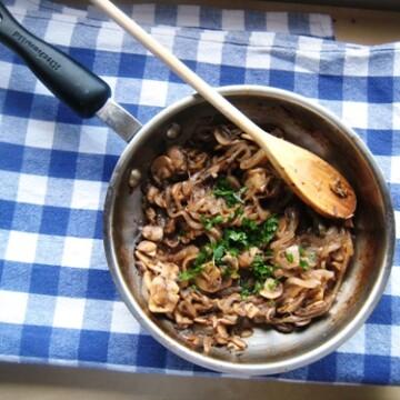 skillet of sautéed mushrooms and onion on a table