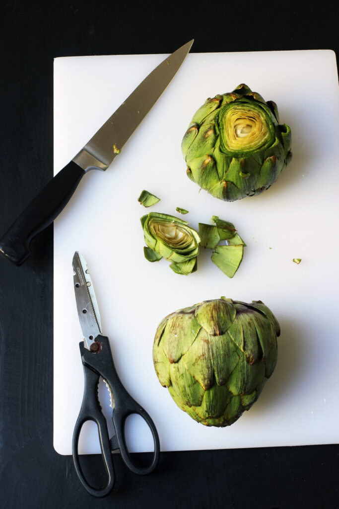 cutting off tip of artichokes
