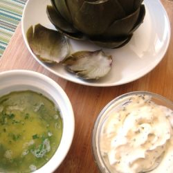 A plate of artichokes and dipping sauces
