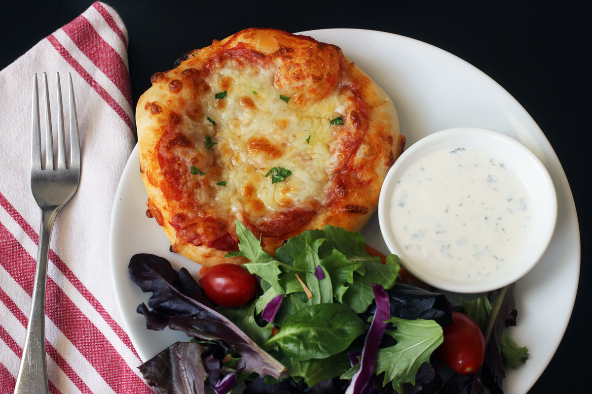 dinner plate with pizza, salad, and ranch dressing