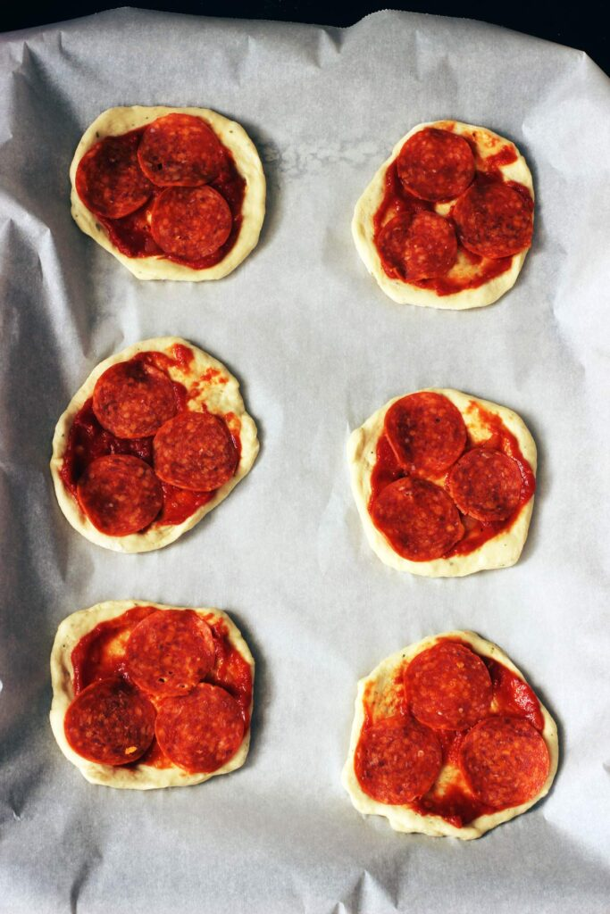 adding pepperoni to pizzas
